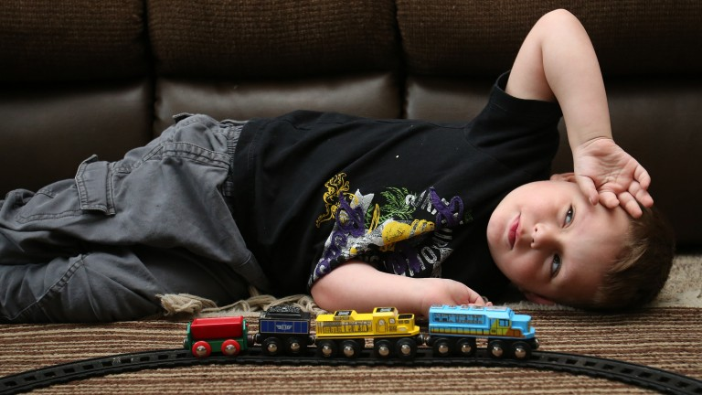Joshua Sekerak takes a break from playing with his train at his home