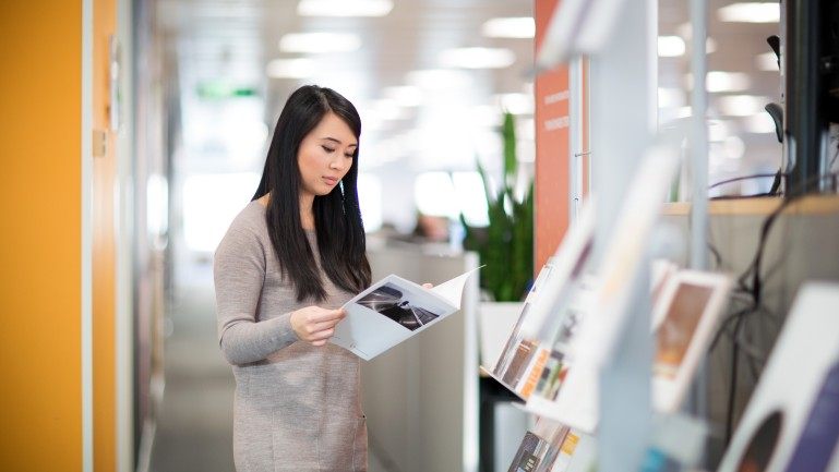 Woman reads brochure standing up in the office