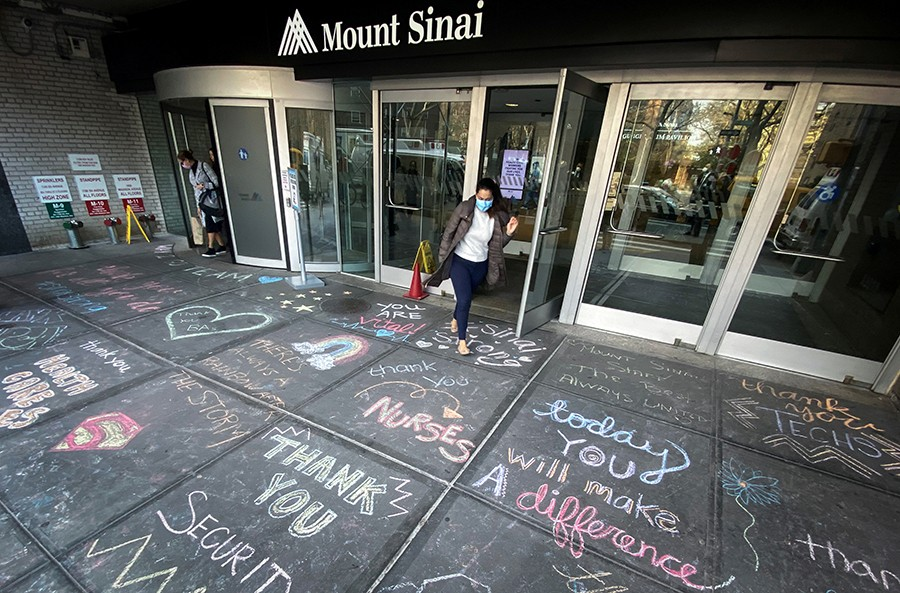 A woman exits Mount Sinai Hospital in Manhattan past messages of thanks written on the sidewalk during the outbreak of the coronavirus disease (COVID19) in New York City, New York, U.S.