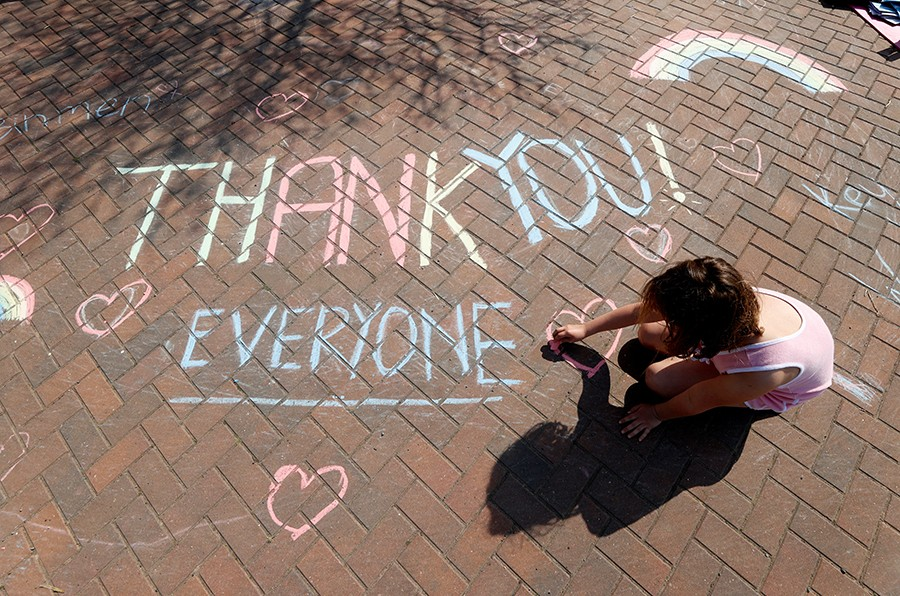 A girl draws a thank you message on the pavement in Broadway as the spread of the coronavirus disease (COVID-19) continues, Broadway, Britain