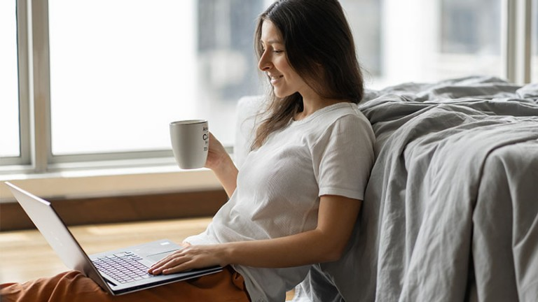 Woman working on a laptop and drinking coffee, sitting on the floor near the bed