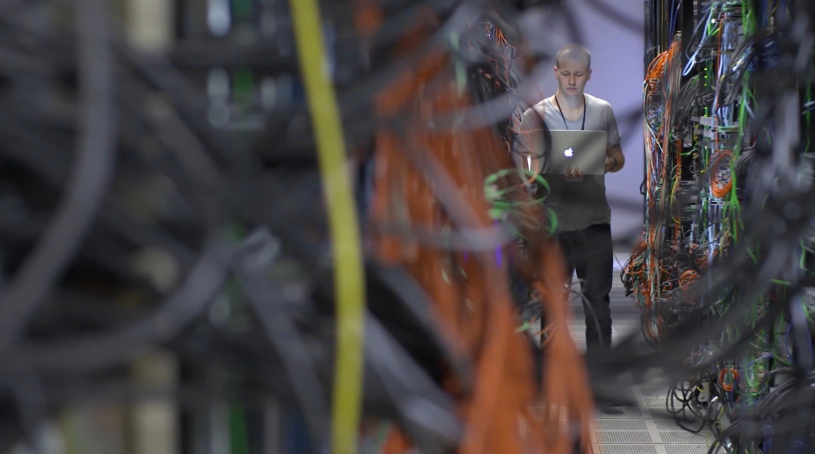 A Cisco employee is seen through cords and servers on Cisco's campus.