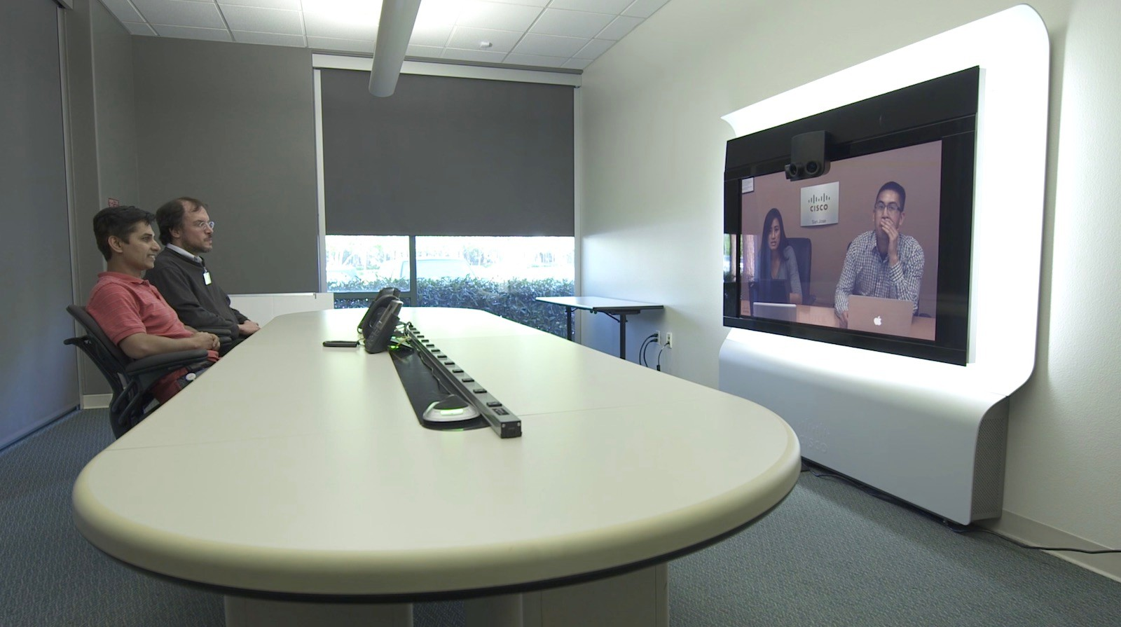 Employees at Cisco's campus use Cisco teleconferencing technology for a meeting.