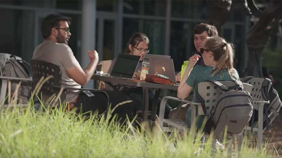 Google employees work outside at a table
