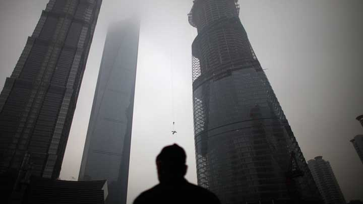 A man watches a construction crane lift a piece of steel at the Shanghai Tower (R) at the financial district of Pudong in Shanghai January 21, 2013.