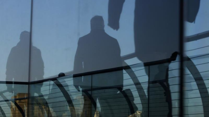 Pedestrians are seen through a glass as they cross the Millennium Bridge in London