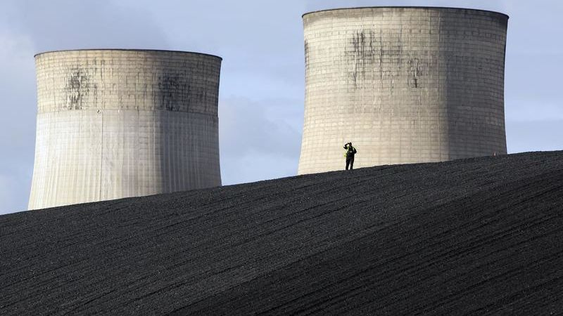 A security guard watches from a coal heap during a climate change protest