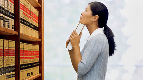 A woman selects reference books from a shelf
