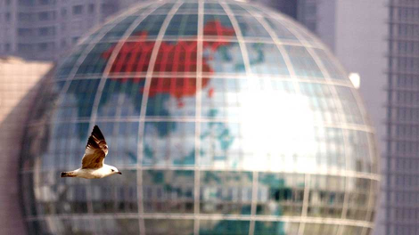 A bird flies past a giant globe-shaped building in Shanghai October 27, 2005.