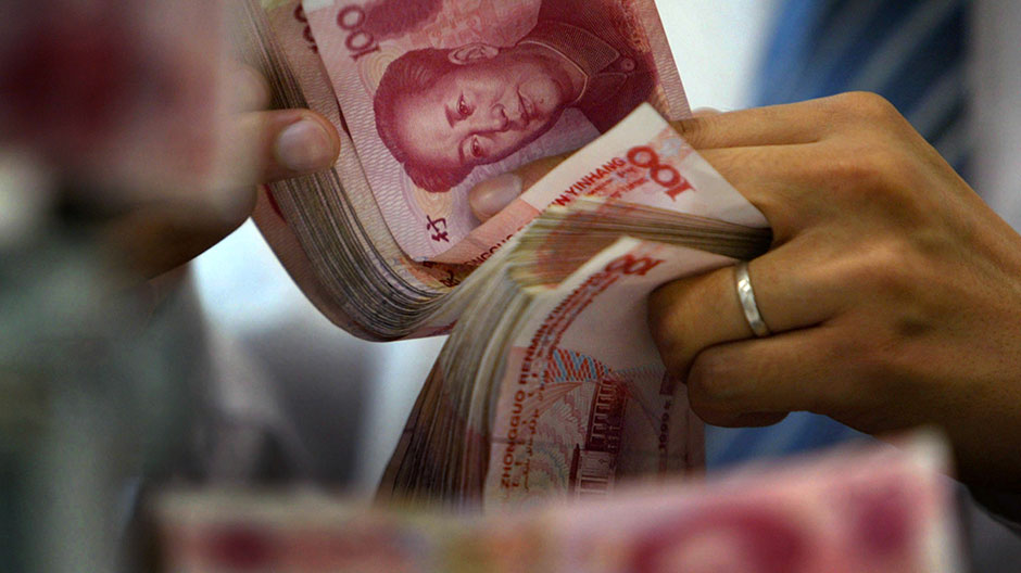 An employee counts yuan notes at a bank in Nanjing, capital of east China's Jiangsu province June 17, 2006.