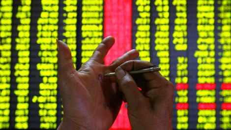 An investor makes a note on his hand at a stock exchange market in Kunming, July 5, 2007.