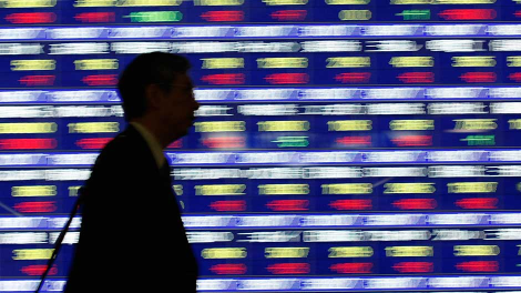 A person walks past a stock quotation board outside a brokerage in Tokyo January 29, 2008.