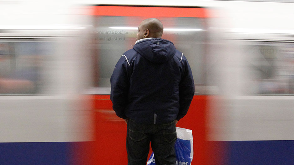 A man waits on a platform as a tube train passes at an underground station in central London January 25, 2010.