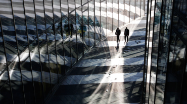 Two men walk past the headquarters of the German postal and logistics group Deutsche Post AG in Bonn March 9, 2010.