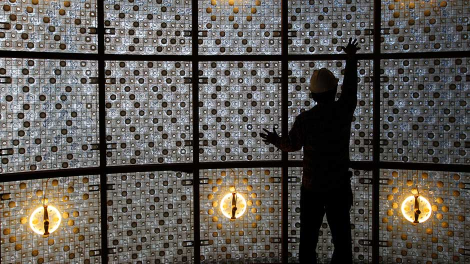 A construction worker touches up a wall made with plastic bottles inside the EcoArk building during a media preview in Taipei April 9, 2010.