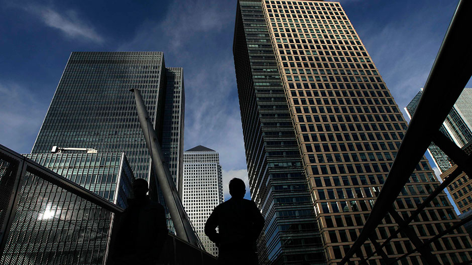 Silhouetted workers walk in front of office towers in the Canary Wharf financial district in London February 16, 2011.