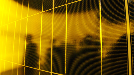 People are silhouetted on a solar panel display by solar module supplier Upsolar at the fourth International Photovoltaic Power Generation (PV) Expo in Tokyo March 2, 2011.