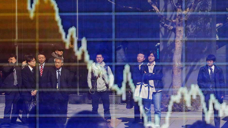 People are reflected on an electronic board displaying a graph showing the movement of the Japanese Yen's exchange rate against the U.S. dollar outside a brokerage in Tokyo March 11, 2011.