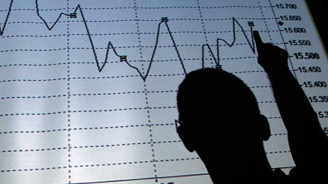 A man is silhouetted in an electronic board showing the FTSE MIB Index for the Italian equity market in this photo illustration taken in Rome August 9, 2011.