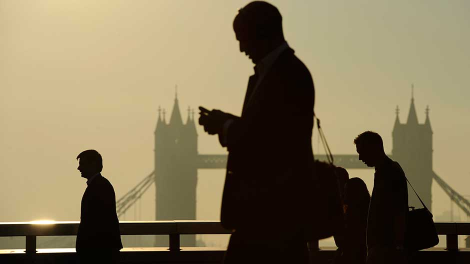 Workers cross London Bridge, with Tower Bridge seen behind, during the morning rush hour in London September 30, 2011.