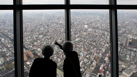Reporters observe a panoramic view of the city of Tokyo from the first observatory deck during a media preview at Tokyo Sky Tree in Tokyo October 30, 2011.