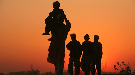 A Muslim man and children are silhouetted against the setting sun on their way to a mosque on the eve of the Eid al-Adha festival in Jammu November 6, 2011.