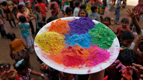 A teacher holds a plate with coloured powder before hurling it on her students as they celebrate Holi, also known as the festival of colours, in the western Indian city of Ahmedabad March 7, 2012.