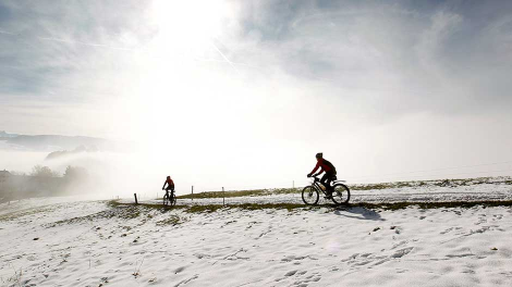 People cycle through the snow-covered landscape near the Swiss village of Hirzel south of Zurich October 31, 2012.