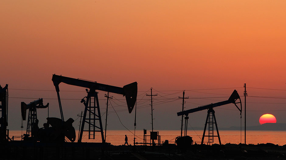 Pump jacks are silhouetted against the rising sun on an oilfield in Baku, January 24, 2013.
