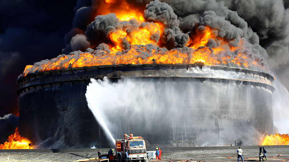 Firefighters work to put out the fire of a storage oil tank at the port of Es Sider in Ras Lanuf December 29, 2014.