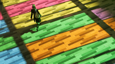 A pedestrian walks through light streaming through colored windows at the Montreal convention center, March 19, 2005.