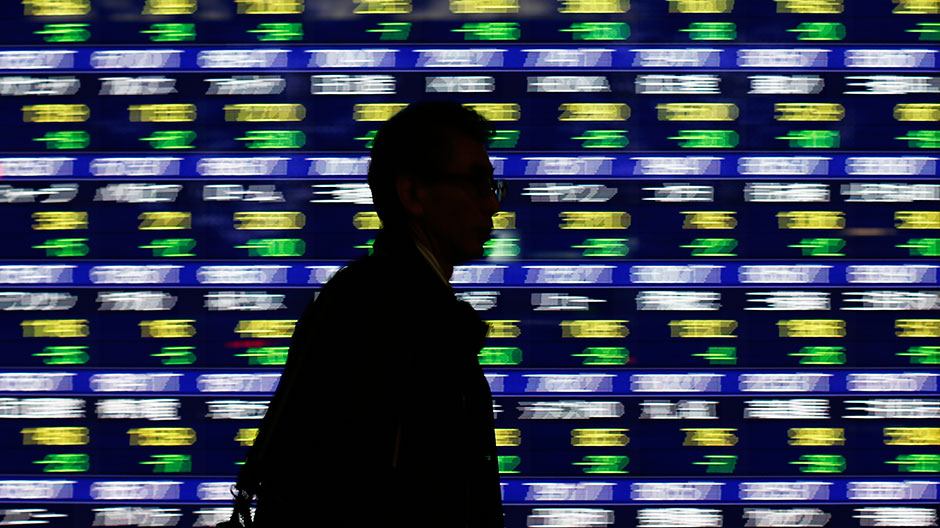 A man walks past an electronic stock quotation board outside a brokerage in Tokyo January 14, 2014.