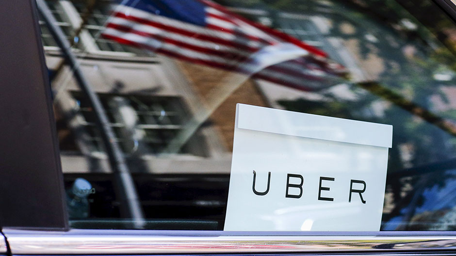 An Uber sign is seen in a car in New York June 30, 2015.