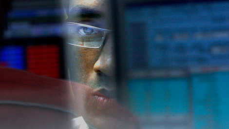 A stock broker looks at a terminal while trading at a stock brokerage firm in Mumbai November 17, 2008.