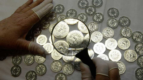 A worker at the Austrian Mint checks five Euro coins for defects in the company's headquarters in Vienna March 11, 2009.