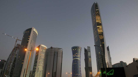 The Navigation Tower (R) stands next to skyscrapers under construction in Doha October 20, 2010.