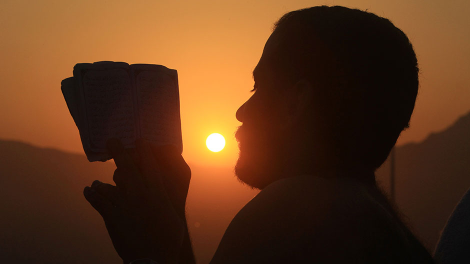 A Muslim pilgrim reads the Koran on Mount Mercy on the plains of Arafat, outside the holy city of Mecca, November 15, 2010.